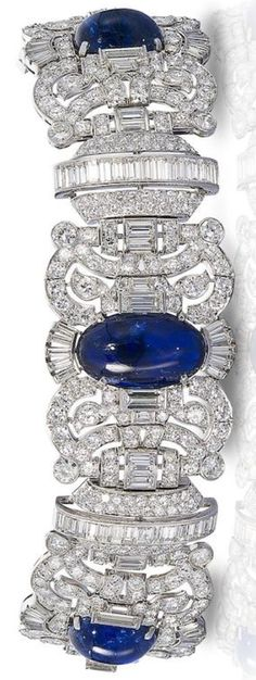 An Art Deco sapphire and diamond bracelet, circa 1935. The wide articulated strap composed of three scrolling openwork plaques, each set with a large sugarloaf cabochon sapphire, within a border of brilliant, baguette and single-cut diamonds, connected by baguette and brilliant-cut diamond buckle-shaped links. #ArtDeco #bracelet