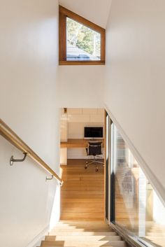These wooden stairs, handrail and window frames break up white walls and ceiling.