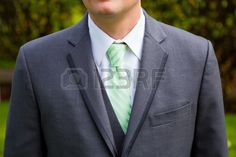 Green tie suit jacket and matching vest worn by the fashion forward groom on his wedding day  Stock Photo