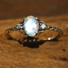 Oval faceted moonstone ring with diamond side set gems in prongs setting with sterling silver twist design band