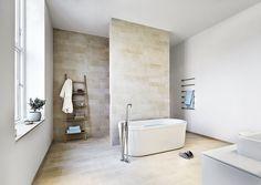 Camelfarvede fliser, Warm Stones White/Gres porcellanato fra Stark, og som kontrast er valgt lyseblå toner i accessories. Badekar og håndvaske er fra Duravit.