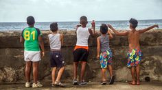 -- Children look out at the Gulf of Mexico from the Malecon, Havana's ocean promenade. Photo by Frank Carlson