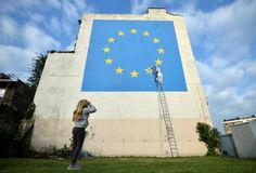 A young girl looks at artwork attributed to street artist Banksy, depicting a workman chipping away at one of the 12 stars on the European Union, seen on a wall in the ferry port of Dover