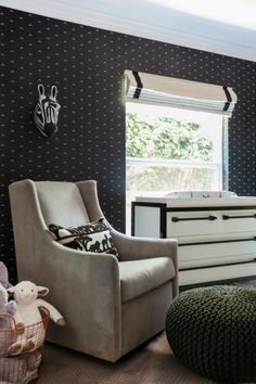 A black-and-white palette and geometric-patterned wallpaper create a contemporary style in this nursery. Wool-covered letters personalize the room, while a plush rug, rocking armchair and cute decorations make it a fun space for baby and parents.