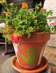 Easy Mother's Day Gift / Memento- hand and foot prints added to cheery clay pot; this one is from 1998; he's 16 now, but I still have his little footprints in my garden.