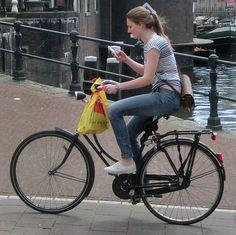 Girl multitasking on old style granny bike. Downtown, Amsterdam.