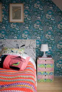 Double bed with colourful textiles next to a small bedside unit and lamp, with blue and white wallpaper behind