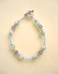 Part of a matching set, with an opal butterfly necklace!  This cheerful beaded bracelet was hand-crafted from sky blue glass paired with striking green-white treated jade and daisy flower fittings.  Enoy :)