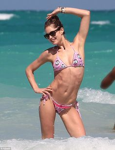 Lean machine: Doutzen worked every one of her muscles as she played in the sun