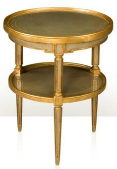 A silvered and gilt verre églomisé two tier circular table, the dished and moulded edge top above a similar undertier, joined by octagonal section supports, on tapering legs by Theodore Alexander. FREE SHIPPING. $1288