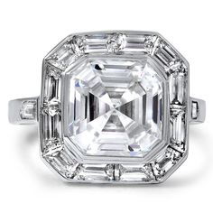 The Percheron Ring, This sensational platinum engagement ring features a bezel-set asscher cut diamond surrounded by a halo of baguette cut diamonds. Two bullet cut diamonds accentuate the sleek shoulders on this marvelous Art Deco ring from the 1930's (approx. 4.35 total carat weight).