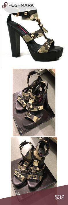 NWT- Dollhouse-Camo Dadam Platform T-Strap Sandal Dare to bare those freshly painted toes in this towering T-strap! An urban camo print with metallic accents gives it cosmopolitan flair, while the adjustable buckle keeps this standout pump in place.   5.5'' heel with 1'' platform Buckle closure Man-made Imported Dollhouse Shoes Sandals