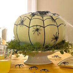 Paint an artificial pumpkin with white acrylic paint; let dry. Use a black paint pen to draw on a web: first draw the vertical lines (follow the veins of the pumpkin), then draw a scalloped horizontal line. Adhere spider webbing to the top of the pumpkin and plastic spiders to the sides using crafts glue.