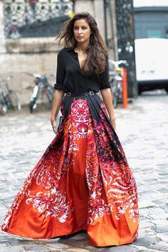 Arrolladora con falda estampada en tonos rojo y naranja con camisa negra ajustada a la cintura con un cinturón de dos hebillas.  If you love this then check out www.partiespearlsandbeingprecious.com