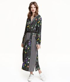Calf-length dress in woven fabric with a printed pattern. V-neck, wrapover top section, removable belt at waist with metal buckle, and long sleeves with narrow, buttoned cuffs. Slits at sides and at front. Unlined.