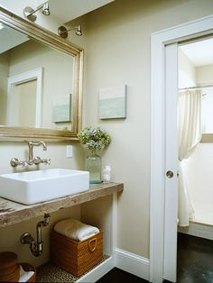 Basement - Bath 6 (3/4) - Love the space saving pocket door.  Touches like repurposed barn door for countertop slab and wall-mount faucet make this room special. #bhg.com