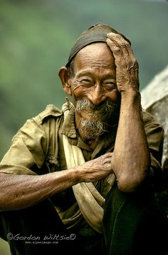 Annapurna foothills, Nepal - An 80 year old rice farmer finally poses after worrying first about his old clothes. - Gordon Wiltsie