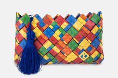 Handmade mini clutch bag based on a pattern illustrating Lego bricks. Accompanied by a blue zipper and and a blue handmade tassel of silk thread for pendant.  The pattern is digitally printed and enriched with a professional photographic plastic; providing UV protection in order to maintain and protect the colors adding 100% waterproofness.