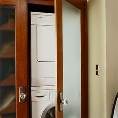 This washer and dryer set sits behind a frosted-glass door. Next to it, laundry storage space hides behind another frosted door.