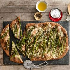 Roasted Asparagus and Fontina Pizza Recipe Main Dishes with olive oil, garlic cloves, asparagus, salt, pepper, all-purpose flour, cornmeal, whole wheat pizza dough, fontina cheese