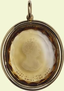 Intaglio of George IV    c.1830    English    First recorded in the Royal Collection in 1914. Oval faceted citrine cut in reverse intaglio with a bust of George IV (1762-1830) in profile to the left. The King is bare headed and wears classical drapery fastened by a brooch on his left shoulder. The front of the citrine is inscribed below the bust: DIED 26TH JUNE 1830.