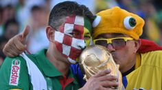 Brazilian fans kiss a replica of the World Cup trophy prior to a Group A
