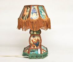A very peculiar vintage table/desk lamp. It is made out of postcards which portray different people; lovers, flowers and landscapes. It is perfect for someone with an acquired taste or someone who is looking for a piece of home decor that will liven up his space and be a great Table Desk, Desk Lamp, Table Lamp, Acquired Taste, Table Vintage, Bulb, Postcards, Landscapes, Lovers