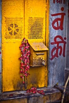 A yellow mailbox Is draped with red flowers left from a Puja...magical India