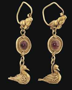 Graeco-Roman gold and garnet earrings, 1st century B.C.-3rd century A.D. Each composed of large hoop with a goat head terminal, with long twisted wire horns, a disc suspended below centred by a cabochon garnet surrounded by bands of twisted, plaited and plain wire, a pendant bird below,  wings, tail feathers feet and eyes with twisted wire decoration, 6 cm high. Private collection