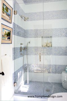 Fun bathroom with glass fronted shower enclosure and Sicis Multi-Stripe Blue and White Glass tiled shower surround.