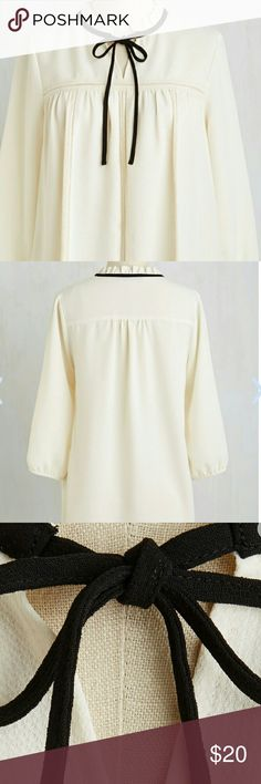 Come by it Modestly You do all things with a demure disposition- like stepping out in this sweet ivory blouse, for example! The image of casual elegance, this 3/4-sleeved top touts a ruffled neckline paired with black piping that leads into a tie, sheer mesh accent panels, and gathering below its yolk. So stylishly prim! Price negotiable Length 28.5 inches 100% Polyester  Fabric doesn't provide stretch  HAND WASH  Semi Shear US Made ModCloth Tops Blouses