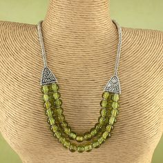 OVERSTOCK.COM $39.99: Add design and flair to your everyday style with this handcrafted glass necklace from Kenya. This handcrafted beaded necklace features recycled glass beads with silver-plated triangle accents.