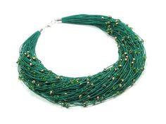 Naszyjnik wykonany ręcznie na bazie przędzy lnianej, w którą wpleciono koraliki szklane w odcieniach zielonej i złotej barwy. Długość naszyjnika około 49cm. Wykończenia posrebrzane.