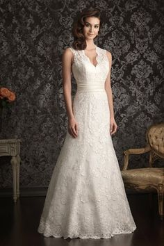 Style No. 9013   A sophisticated design with beautiful details. This slim line gown features delicate lace throughout. The bodice has a dramatic v-shaped neckline and beautiful key-hole back while a chapel length train finishes the dress perfectly.