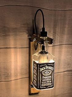 "Price: $95.00USD This lamp is made entirely by hand from authentic old oak barrels of 1966 and a bottle of whiskey ""JACK DANIELS"" with both arms and fly nuts you can adjust the position that is best for you. The design is maintained in an old industrial style. Every element has #Bottlelamp #Industrial #Kitchendesign #Led #Lightingdesign #Oak #Sconce #Vintagelighting Whisky Jack Daniels, Lampe Jack Daniels, Jack Daniels Bottle, Jack Daniels Decor, Jack Daniels Gifts, Alcohol Bottles, Liquor Bottles, Vintage Industrial Lighting, Industrial Style"