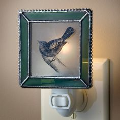 """J Devlin NTL 119-2 Bird Night Light Moss Green. Framed in moss green stained glass and a decorative metal edging. Clear sand etched glass with an image of a bird in pin and ink fired on in a kiln. 4 watt bulb included. Handcrafted stained glass night light made with lead free solder to protect you and the environment. Designed and Manufactured by J Devlin 3"""" x 1 1/2"""" x 4 1/2""""."""