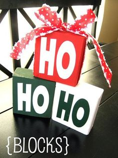 HO HO HO Blocks: All you need are some leftover 2x4's cut into 3 blocks, some HO HO HO vinyl, ribbon & paint. Paint your blocks red, green & white.  Let dry and then apply the vinyl lettering. Stack them up. Add some Christmas ribbon & that's it. Super cute! #BlockWoodCrafts