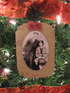 I copied the original photo of my maternal great-grandparents onto regular office paper and the result was a picture that glowed backlit by the tree lights. The frame of this ornament is from a pre-made family history album somebody bought for me to plug photos into. I didn't the book's layout so I cut it up and used the pieces as frames for ornaments instead. There are a few variations. I did a double fabric rose at the top of this ornament and edged the corners with a corner rounder.
