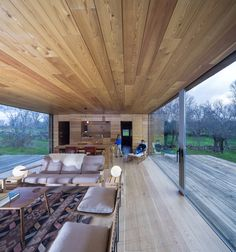 The B-House by ch+qs arquitectos, spain: The house itself is nothing but an enormous room with sliding glass walls facing east and west. It's wrapped in yellow wood planks. Decks of the same wood appear to be cut of out the structure, replaced by the glass.