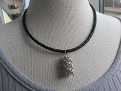 Braided leather necklace with a cage bead chainmaille pendant.