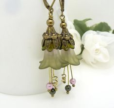 Lovely dark olive green lucite flower earrings, with touches of pink, sage green pearls and olive green crystals  These pretty green flower earrings were made using:  ~ Dark olive green and pink lucite flowers ~ Sage and olive green swarovski pearls ~ Antique bronze beads and ear wires  The earrings measure 2 inches from top to bottom  Thanks for stopping by to view my green flower earrings  To see more of my vintage and gothic inspired jewelry visit my store: http://www.etsy.com&#x...