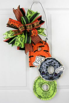 "A B-O-O door hanger with a happy little ghost peaking out. This is the perfect size and lightweight for your Halloween decor, all tied with a multi-patterned Terri Bow. Measures 27""H X 14""W."