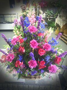 Basket Arrangement with Liatris, Delphinium, Purple Statice, hot pink carnations and roses.