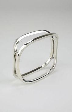 A solid silver split rectangular bangle - a rare design of two lozenge shapes made of square rod which are curved away from one another but float above each oth