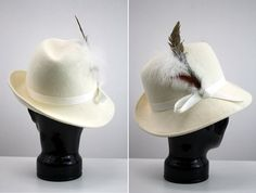 Winter white is the best! And so is this hat. The feather accent adds a powerful punch to this chic accessory. Small stain on part of the hats ribbon.