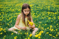 Untitled - Little girl collecting dandelion flowers.