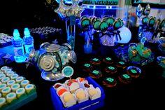 detalhes da mesa do bolo com docinhos e pirulitos personalizados para uma festa teen com tema balada para menino de 10 anos. As cores escolhidas foram azul turquesa e preto.