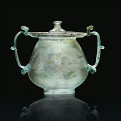 A RARE GALLO-ROMAN BLUE-GREEN BLOWN GLASS LIDDED URN OR CINERARIUM 1ST-2ND CENTURY A.D. The large globular body with concave base, the wide everted rim hollow-folded outwards to form a flat tubular rim, two large vertical trailed glass handles attached to rim and lower belly of the urn, each with pinched ornamental fold at base, in the centre and at the top, the lid with perforation through the knob, traces of purple iridescence around the rim11 5/8 in. (29.5 cm.) high incl. lid