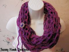 Fashion Statements Infinity Scarf – Crocheted scarf in shades of purple with rhinestone button tie. Versatile styles in one scarf.