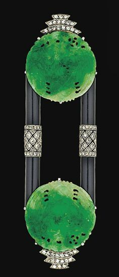 An Art Deco jadeite jade, onyx and diamond brooch  Set with two circular carved and pierced jade plaques with tiered old single-cut diamond terminals, connected by onyx baton links with central diamond-set pierced lattice motif, circa 1925
